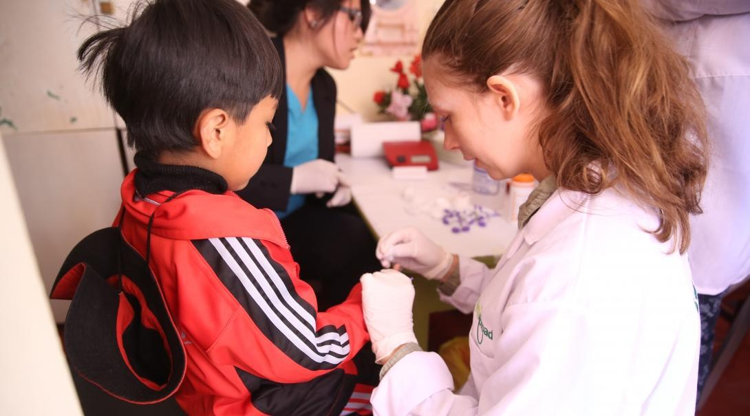 A female intern from Projects Abroad is seen drawing blood from a childs finger as part of her nursing internship in Peru.